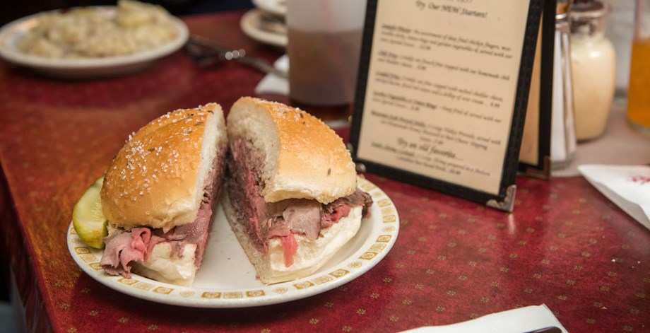 Beef on Weck features thinly sliced roast beef piled high on a kimmelweck roll.