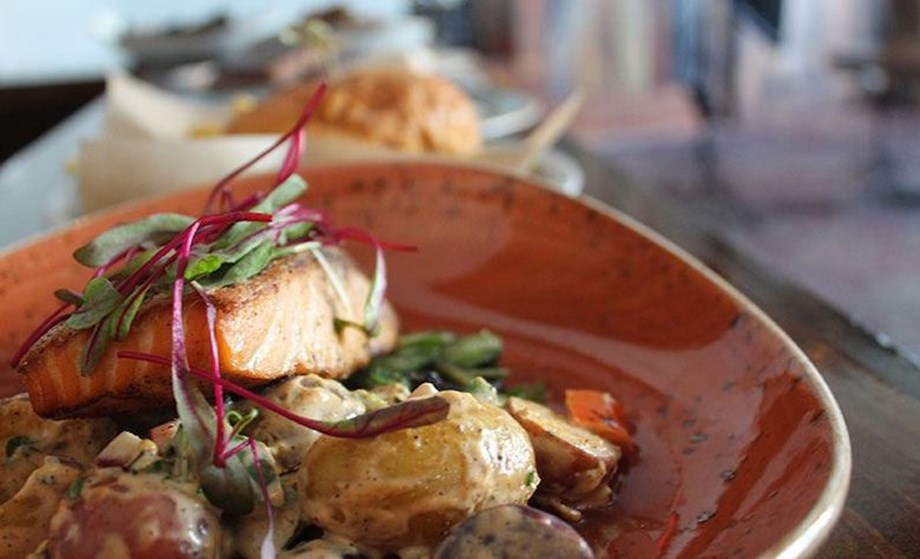 Rye Bar's hickory salmon entree is served with creamed mustard greens and marble potatoes
